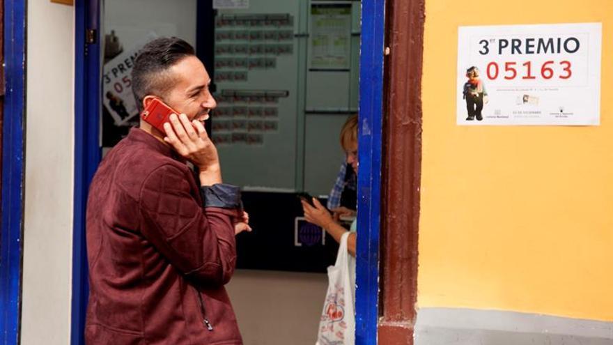 El propietario de la administración número 9 de Santa Cruz de Tenerife, Hari Satyani, conversa por teléfono, tras conocer que ha vendido por máquina un tercer premio del sorteo de la Lotería de Navidad