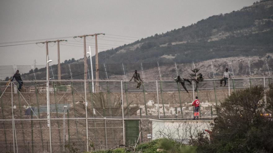 Varios inmigrantes permanecen encaramados en la valla interna de Melilla, mientras una persona de Cruz Roja interviene para intentar ayudar a bajarlos. Esta escena se produce después del salto coordinado de la alambrada con el que lograron su objetivo de acceder a territorio español 250 personas. /Jesús Blasco de Avellaneda