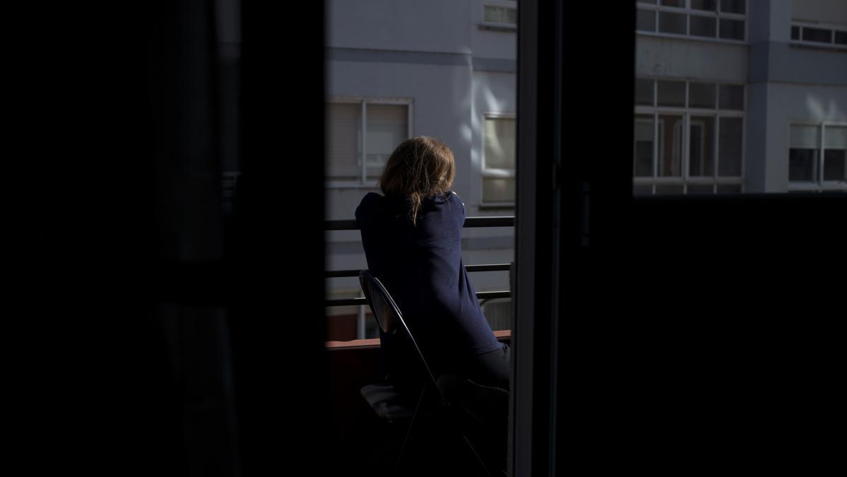 Una persona joven se asoma por la ventana.