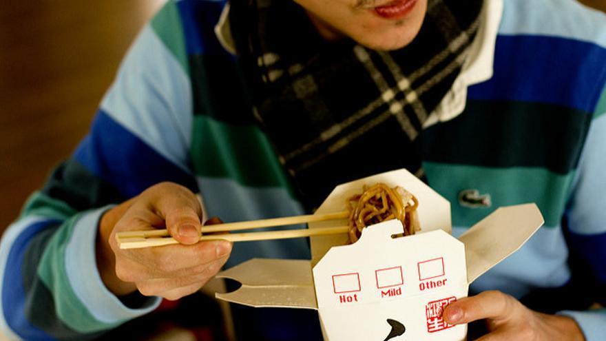 Un home menjant menjar preparat / CC by-sa Maurice Svay (Flickr)