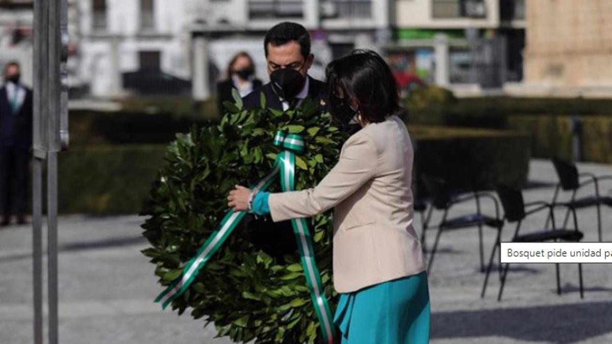 El presidente de la Junta de Andalucía, Juanma Moreno, y la presidenta del Parlamento, Marta Bosquet, realizan una ofrenda floral en el acto por el Día de Andalucía en recuerdo de los fallecidos por la pandemia.