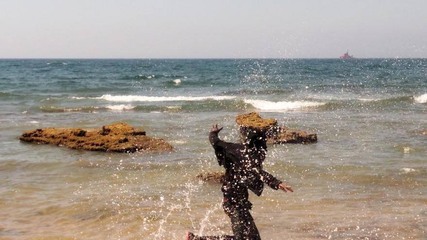 Uno de los migrantes que viajaba en la embarcación hinchable salta y celebra la llegada a tierra