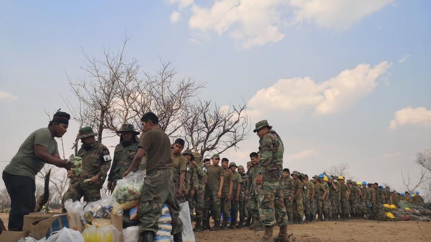 Un grupo de soldados hacen cola para recibir alimentos y botiquines donados por un grupo de mujeres que se asociaron en redes sociales.