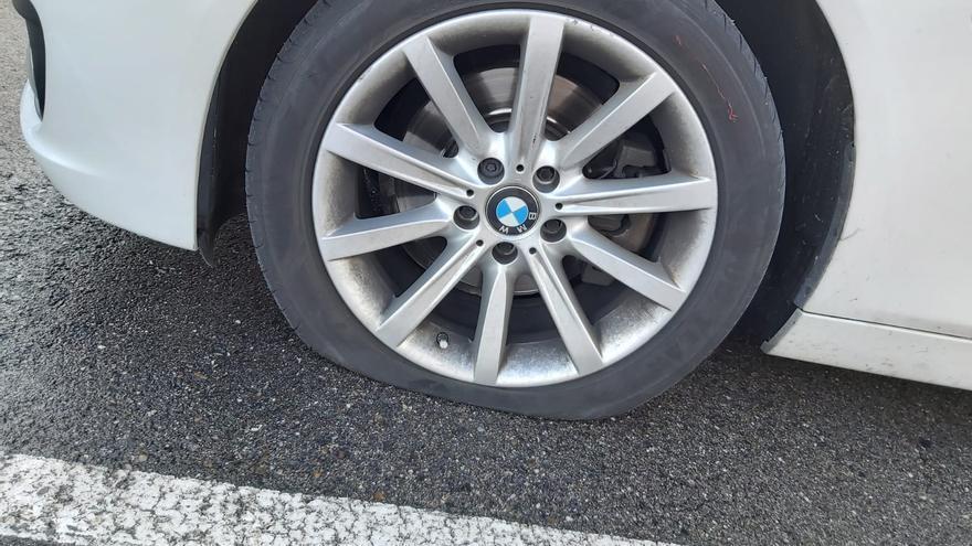 La rueda pinchada del coche de uno de los agentes.