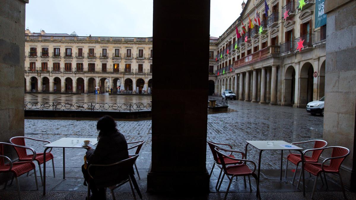 Una mujer toma un café en un bar de Vitoria