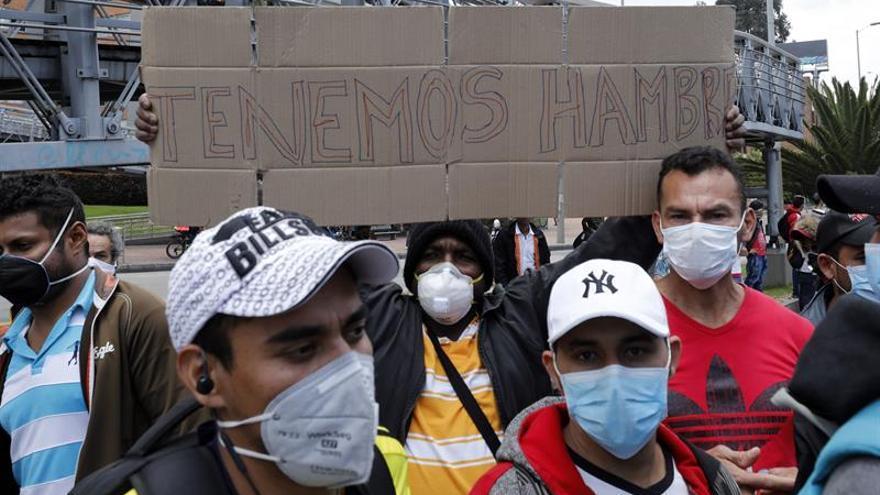 Un grupo de ciudadanos protesta este miércoles, en Bogotá (Colombia). A pesar de que la cuarentena por el coronavirus está vigente, decenas de colombianos se manifestaron este miércoles en un sector del norte de Bogotá para hacerle a las autoridades una petición concreta: que les donen alimentos o les permitan trabajar.