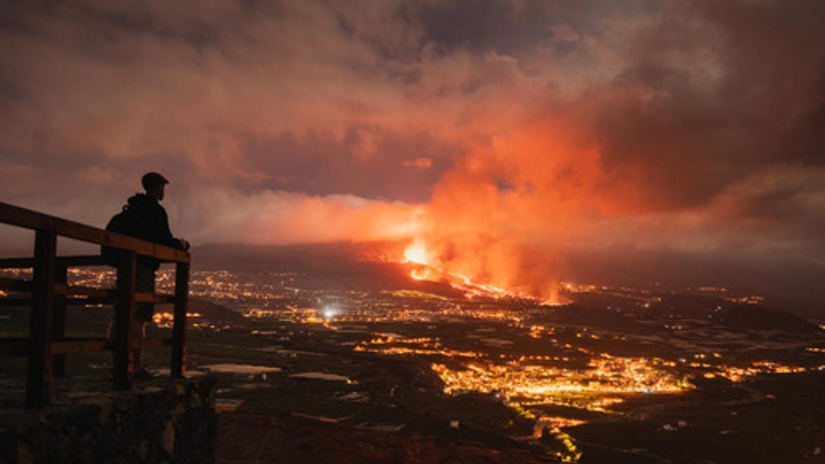 Una persona observa desde un mirador la actividad del nuevo volcán de La Palma