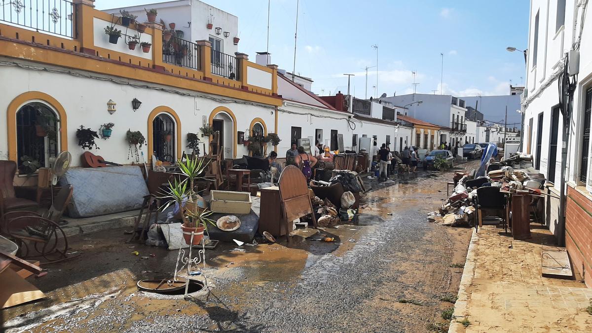 Vecinos sacan sus enseres dañados en una calle de Cartaya (Huelva) tras las fuertes lluvias caídas este jueves en el litoral onubense. EFE/ Juan Ernesto García-Chicano