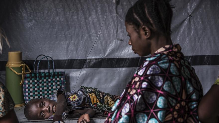 Una mujer mira a un niño que sufre de cólera grave que se encuentra en observación.