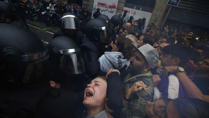 Agentes de la policía nacional forcejean con una mujer que intenta votar en el colegio Ramon Llull de Barcelona.