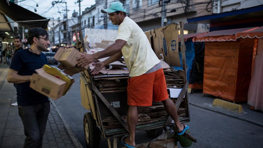 """Augusto recoge cartones de un comercio para colocarlos en su carro. Los catadores llaman a estos carros """"burrinhos sem rabo"""", o sea, burros sin rabo.   Foto: Patricia Taro."""