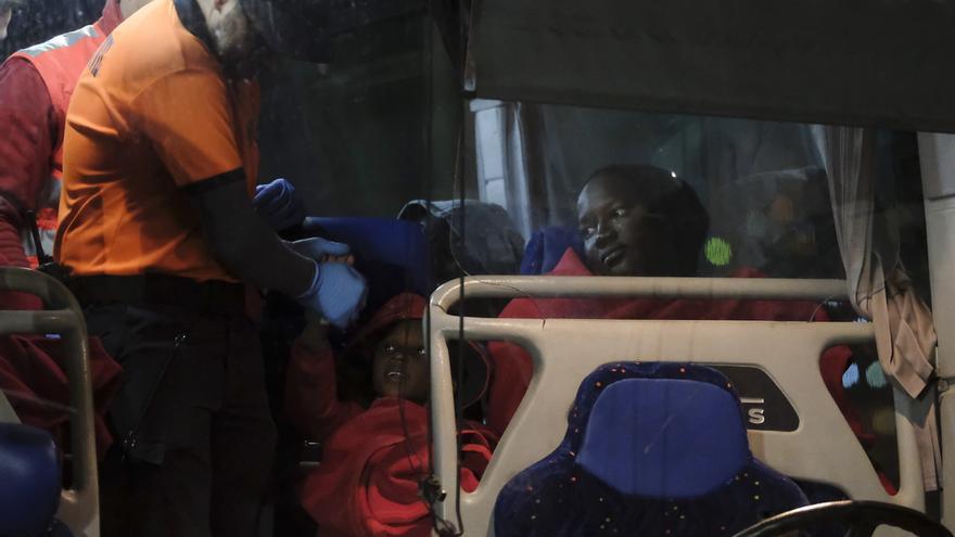 Un voluntario de Protección Civil juega con uno de los seis niños que viajaban a bordo de una patera localizada este miércoles a 150 kilómetros de Gran Canaria con 33 personas a bordo.