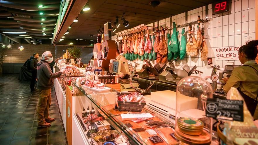 Varios clientes hacen la compra en un puesto de carne y embutidos (Archivo)