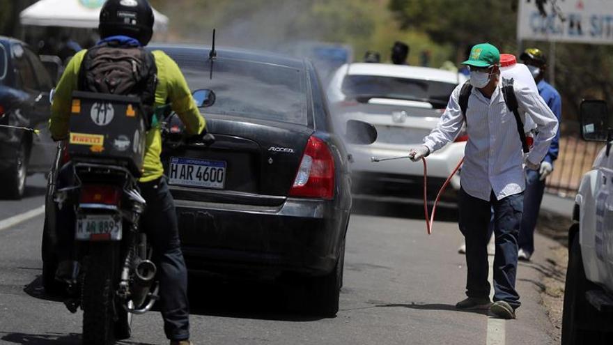 Autoridades hondureñas desinfectan vehículos que entran al municipio de Santa Lucia, este lunes, al noreste de Tegucigalpa (Honduras).