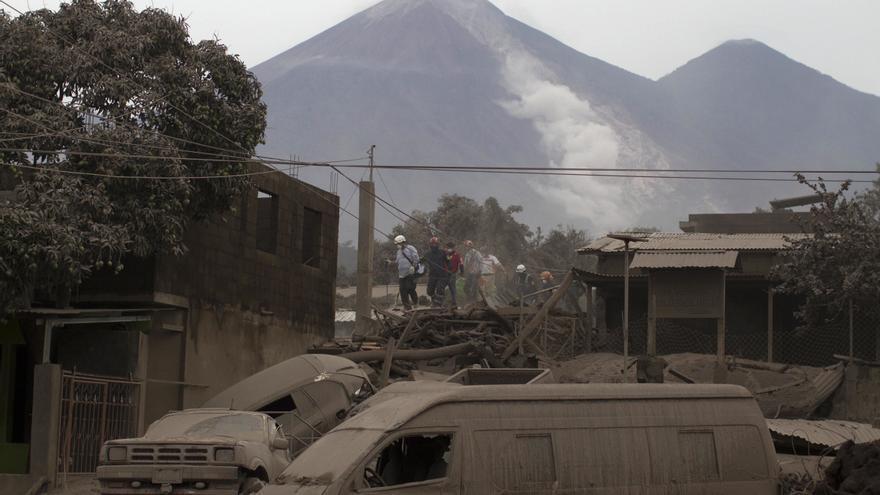 Los trabajadores de rescate caminan por los tejados de Escuintla, Guatemala, este lunes, cubiertos con cenizas pesadas arrojadas por el Volcán de Fuego. Foto AP / Luis Soto