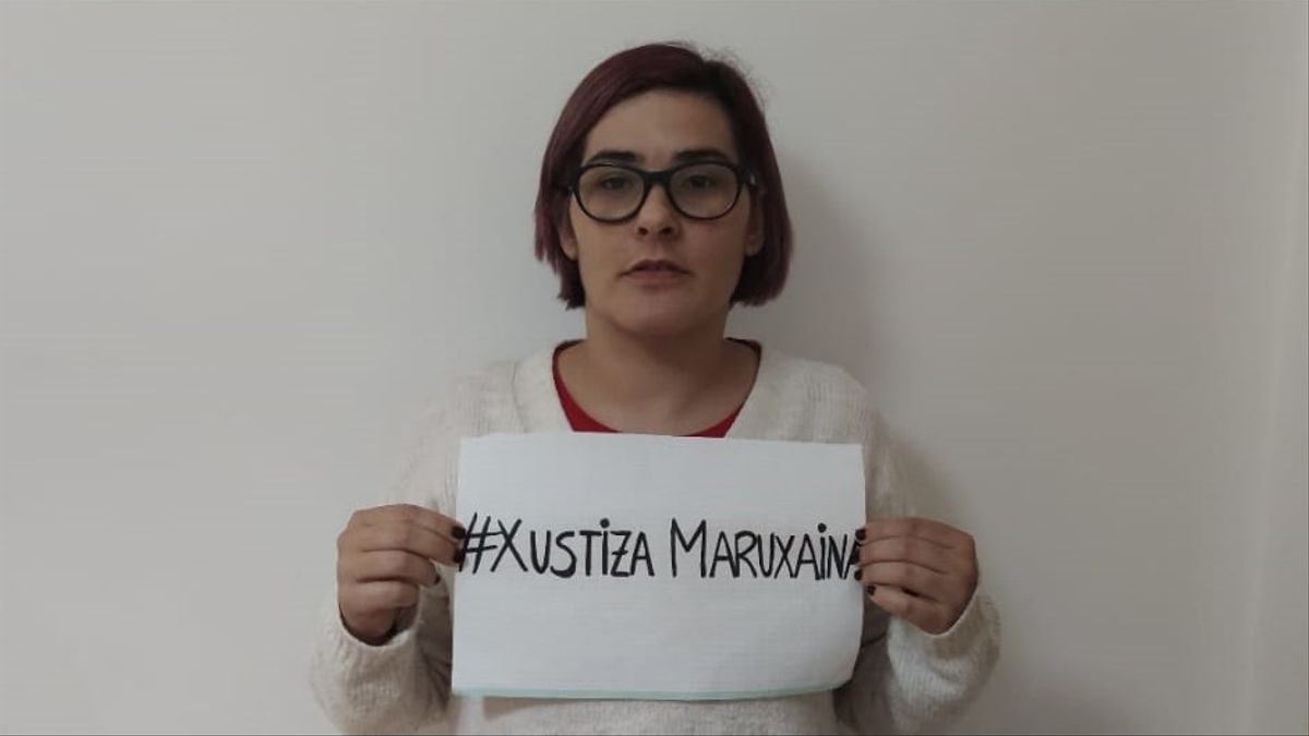 Paloma Maseda muestra un cartel en el que pide justicia para su caso y el de otras mujeres grabadas orinando