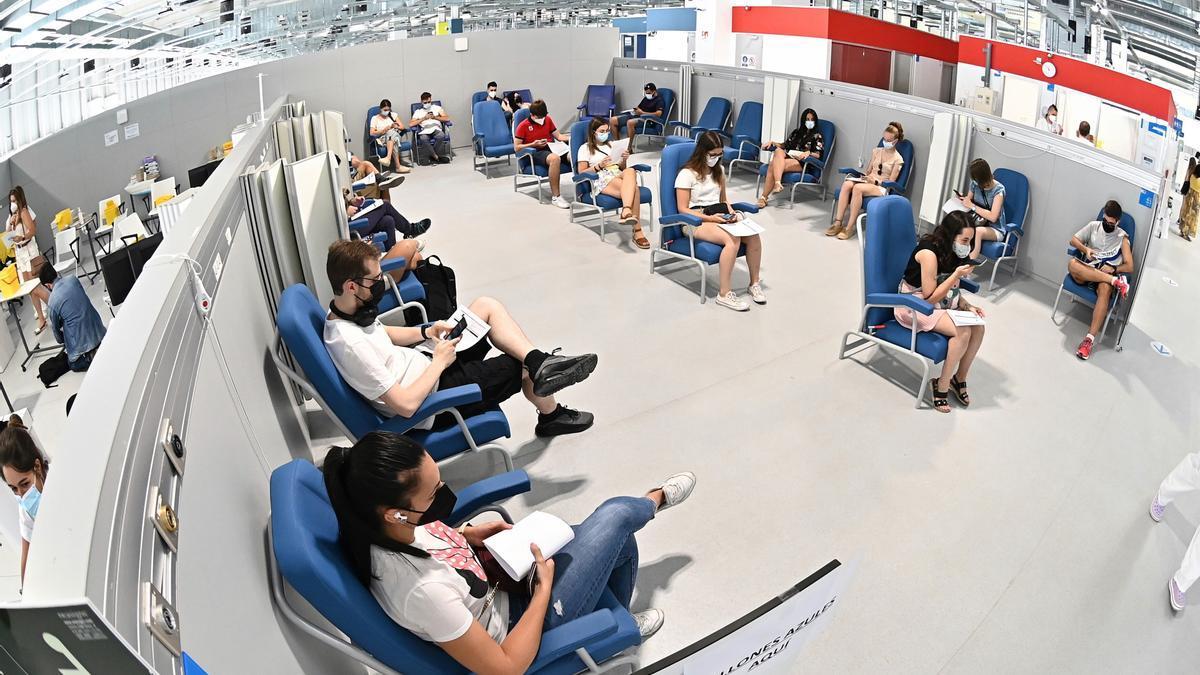 Cientos de personas, entre los que se encuentran los jóvenes mayores de 16 años, esperan en el hospital Enfermera IsabelZendal de Madrid, tras ser vacunados frente al coronavirus. EFE/ Fernando Villar