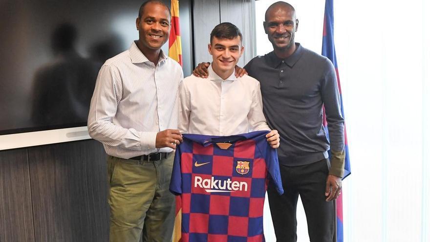 Pedri junto a Abidal y Kluivert posando con la camiseta del FC Barcelona.