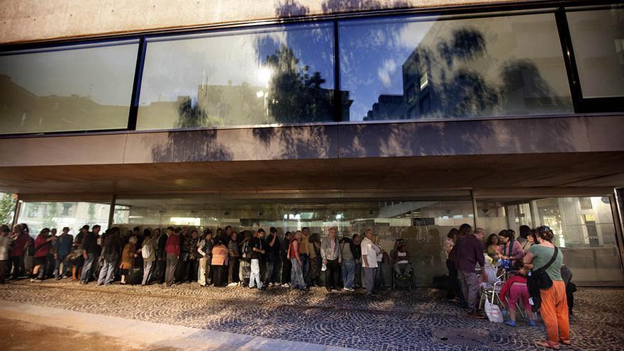 Ciutadans sense recursos fan cua per recollir el sopar calent que BarcelonActua els ofereix cada dijous a la Rambla del Raval (Carmen Secanella)