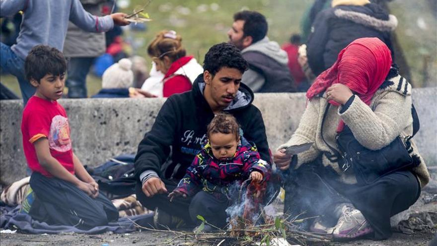 Una familia de refugiados aguarda en la frontera entre Austria y Eslovenia en la ciudad Spielfeld, en la región de Estiria (Austria)./ Efe.