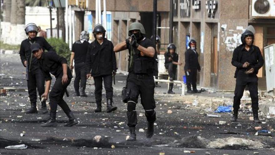 Un policía egipcio se dispone a disparar un bote de gases lacrimógenos contra unos manifestantes (EFE archivo)