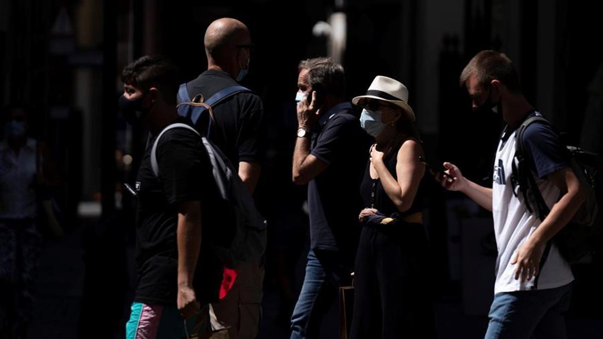 Varias personas caminan por las calles de Santa Cruz de Tenerife haciendo uso de mascarillas.