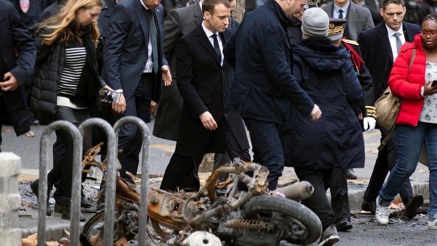 Emmanuel macron pasa junto a una motocicleta calcinada mientras comprueba personalmente los daños materiales ocasionados en las protestas de los chalecos amarillos