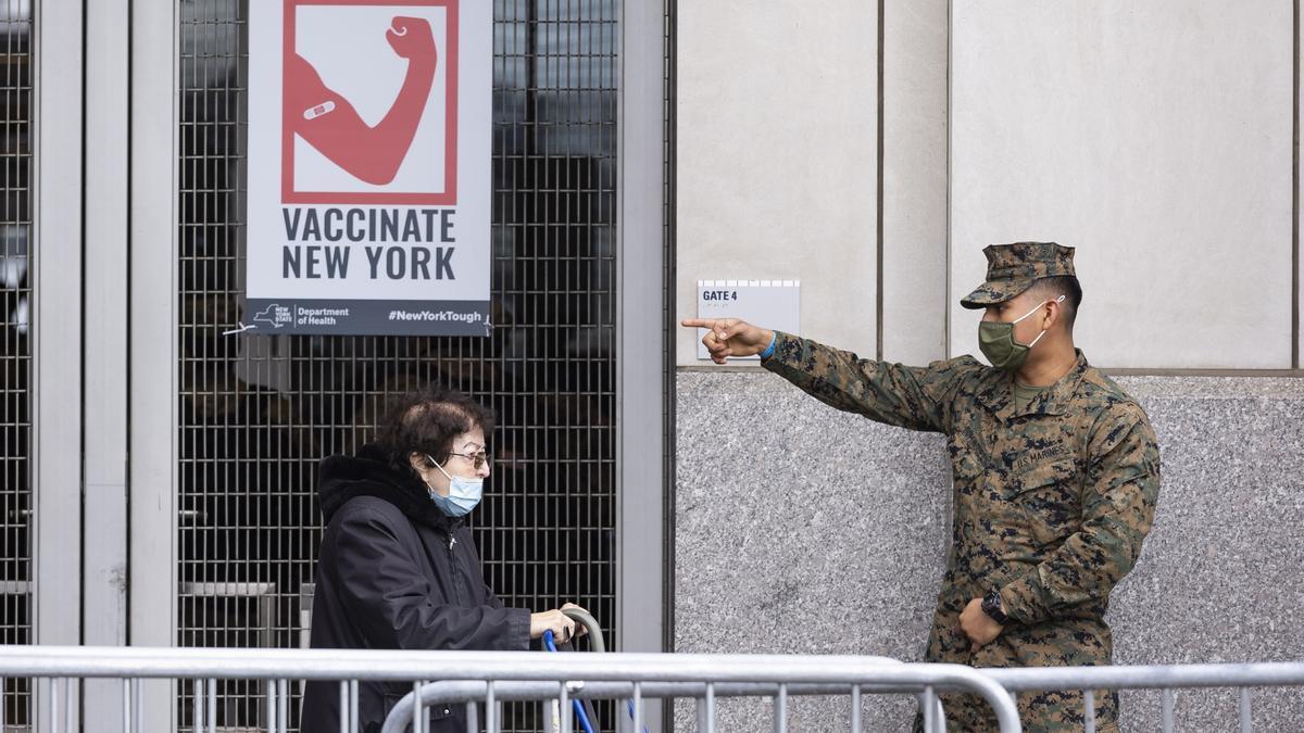 Un miembro de la Guardia Nacional indica a una mujer el acceso al centro de vacunación del estadio de los Yankees de Nueva York.
