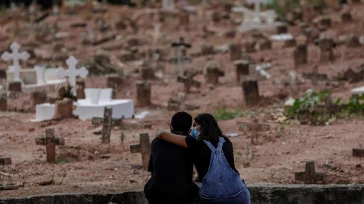 Una pareja llora a una mujer víctima de Covid-19 que fue sepultada este 6 de abril de 2021 en un cementerio de Río de Janeiro, Brasil.