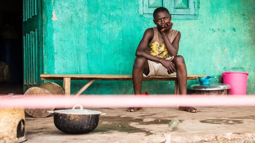 Un joven en cuarentena tras un cordón frente a su casa en la ciudad de Moyamba, en las afueras de Freetown, Sierra Leona, octubre de 2014 (AP Photo / Michael Duff)
