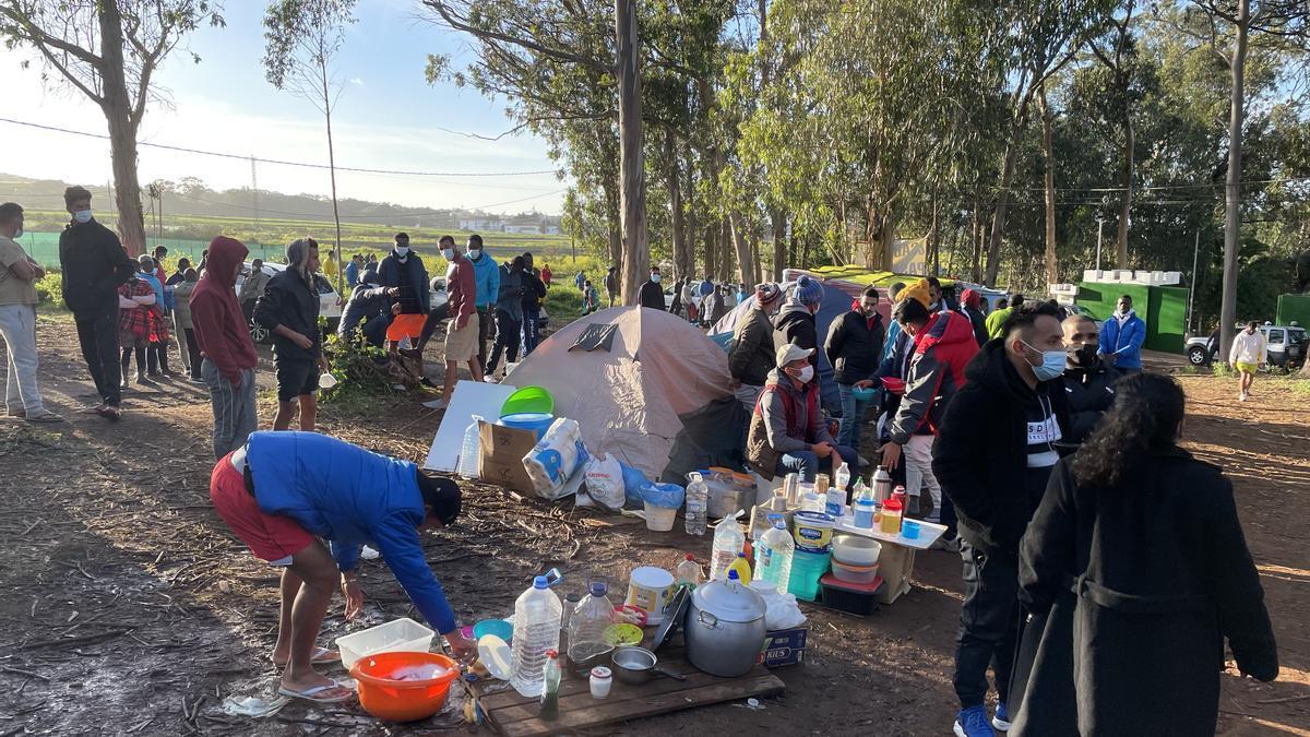 Migrantes en el exterior del campamento de Las Raíces
