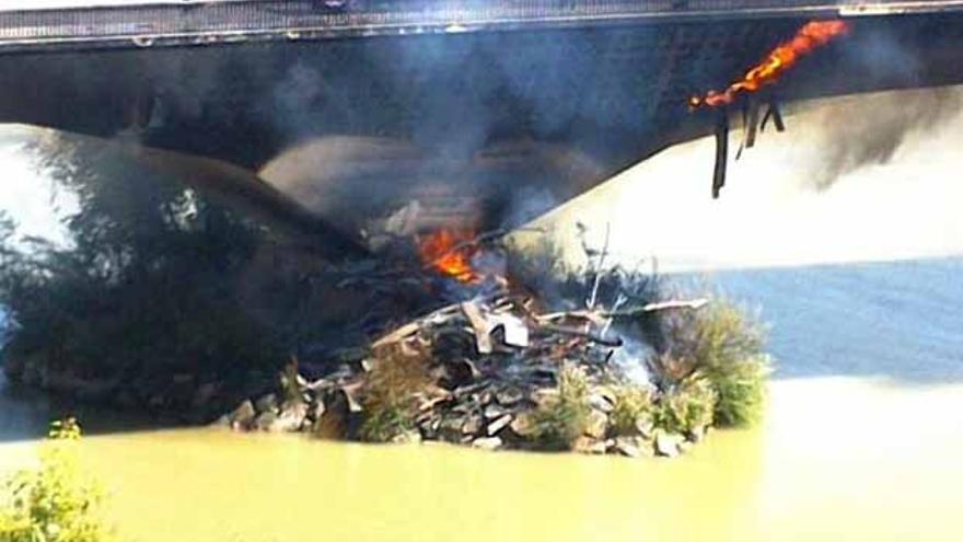 Las llamas afectando, hace un momento, al pilar del Puente del Arenal. | FOTO: ÁLVARO CARMONA