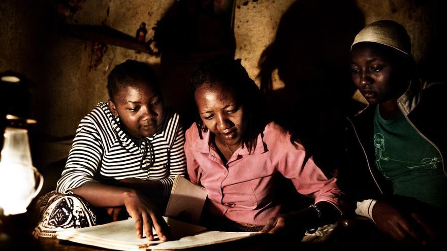 Las tres hermanas observan el Memory Book que les dejaron sus padres. Lilian (a la izquierda) es la madre del único niño que vive de momento en el hogar. Grace, la mayor de todas, está sentada en medio, junto Rose, la más pequeña y la que menos recuerdos tiene de sus progenitores. En Moshi, Tanzania. / Foto: Álvaro Laiz y David Rengel. / AnHua