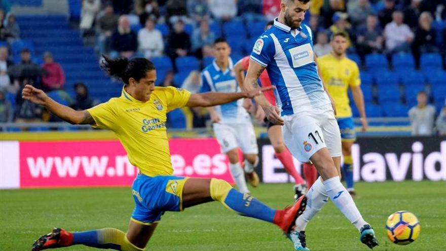 El defensa uruguayo de la UD Las Palmas Mauricio Lemos (i) lucha el balón con el brasileño Leo Baptistao, delantero del RCD Espanyol.