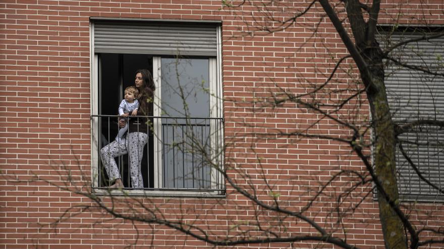 Madre y su bebé mirando por la ventana
