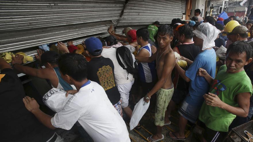 Habitantes de Tacloban intentan abrir una tienda para coger comida