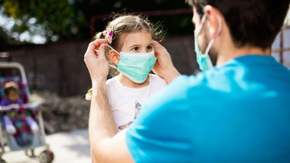 Un profesor coloca una mascarilla a una alumna de Infantil. Archivo.