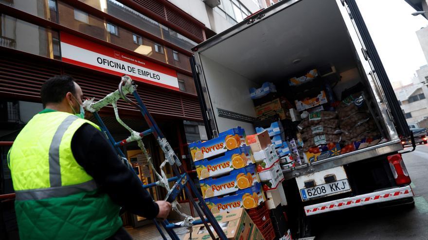 Un operario descarga la mercancía de un camión junto una oficina de empleo en Madrid.