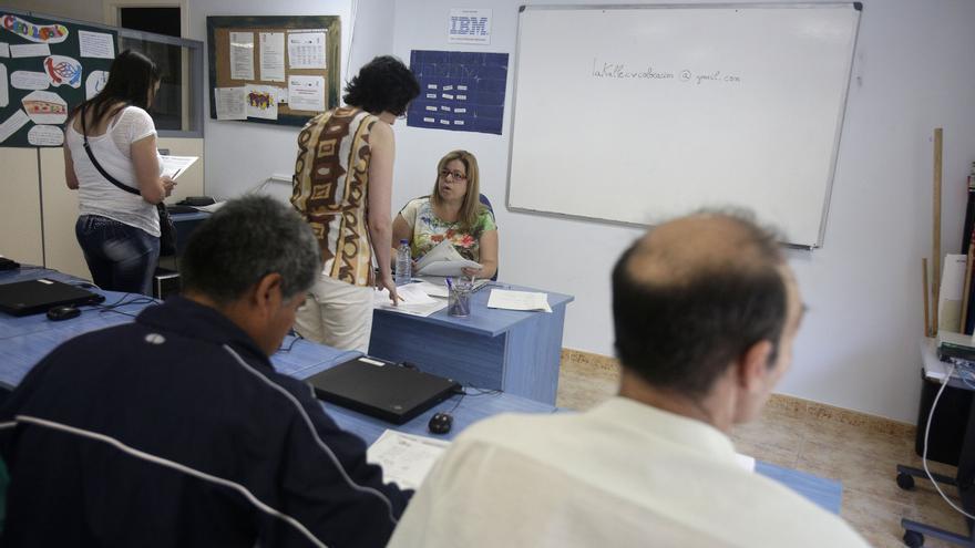 Varias personas asisten a un curso en la Asociación Lakalle de Vallecas, Madrid. Foto: OLMO CALVO