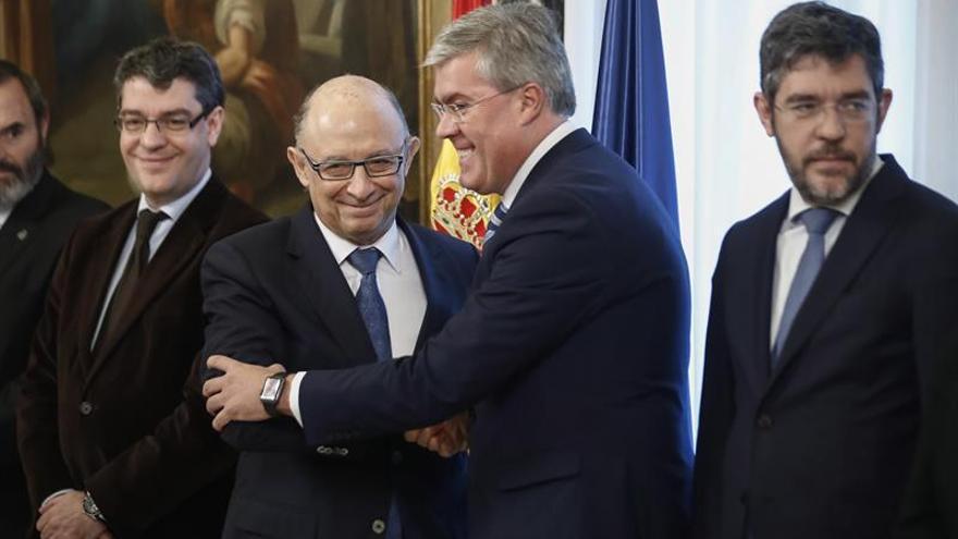 El ministro de Hacienda, Cristóbal Montoro, estrecha la mano del secretario de Estado de Hacienda
