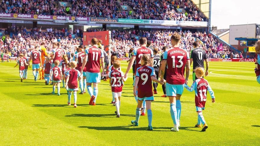 Jugadores del Burnley acompañados de niños que han pagado hasta 310 libras por salir al campo de la mano