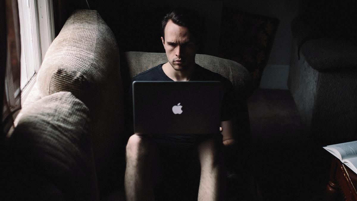 Un hombre utiliza un ordenador en su casa