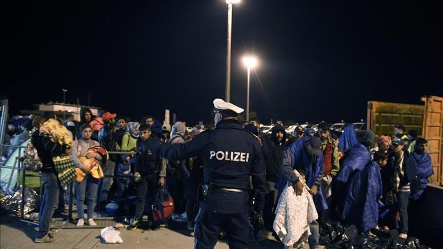 Refugiados que cruzaron la frontera desde Hungría son guiados a un refugio en la madrugada de este jueves, 10 de septiembre de 2015, en Nickelsdorf (Austria) como escala previa a su deseado destino final: Alemania. / Efe.