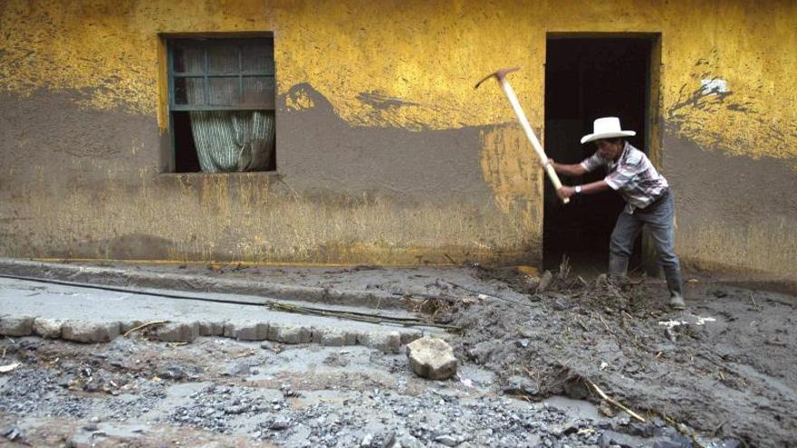 Un campesino retira lodo de su casa, en una de las calles principales de la localidad de San Antonio Senahú.
