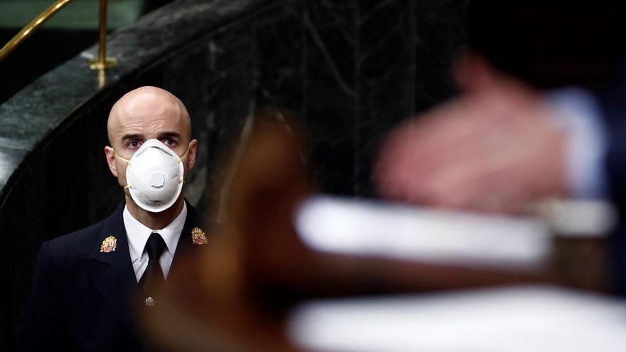 Un ujier del Congreso con mascarilla observa el debate de la prolongación del estado de alarma.
