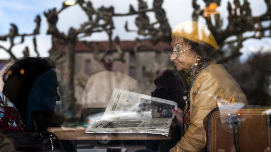 Una mujer consulta el periódico en un bar de Santander. | JOAQUÍN GÓMEZ SASTRE