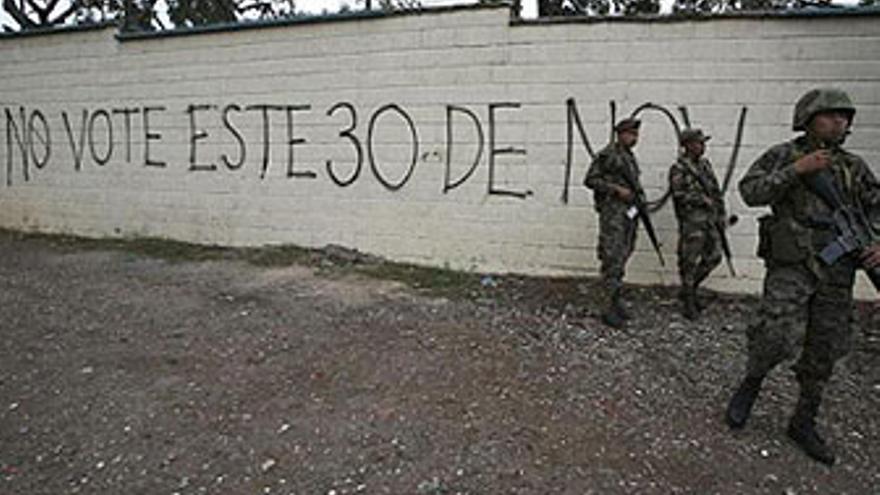 Militares hondureños de patrulla, ante una pintada contra las elecciones de este domingo. (EP)