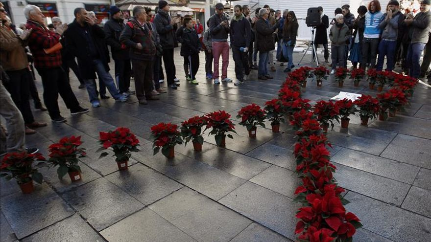 Lazo rojo formado por poisenttias durante un acto conmemorativo organizado por CESIDA.