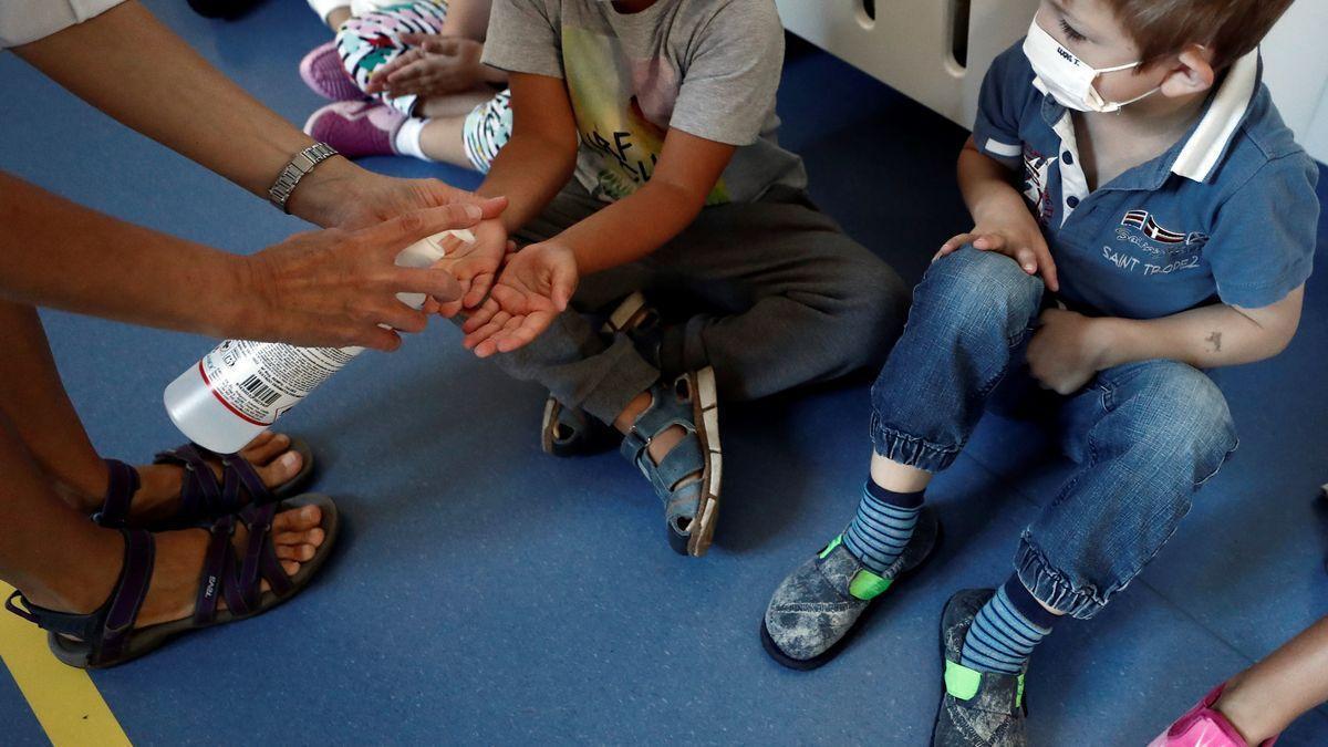 Un profesor echa gel hidroalcóholico a un grupo de niños con mascarilla en el colegio.