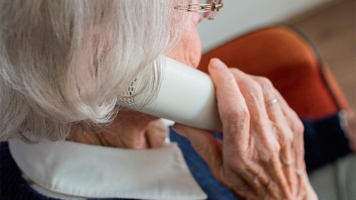 Una mujer mayor llama por teléfono.